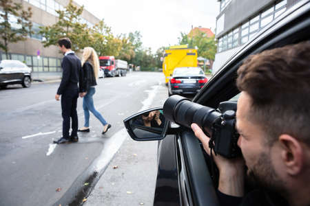Young Male Spy Sitting In The Car Taking Photograph Of A Couple Walking On Street