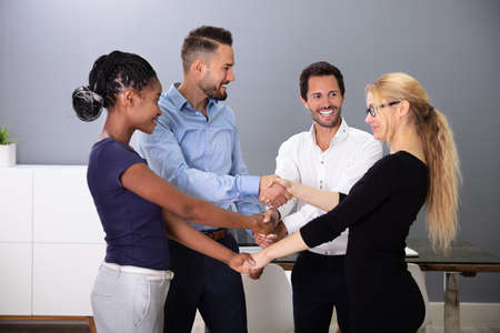 Group Of Multi Racial Businesspeople Shaking Hands With Each Other In Office