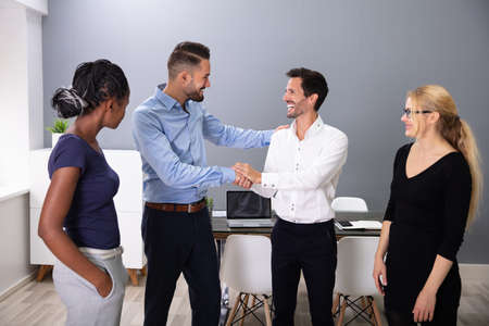 Women Looking At Happy Young Business Men Shaking Hands In Meeting Room