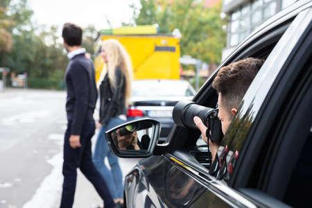Détective privé prenant des photos d'un homme et d'une femme dans la rue Banque d'images