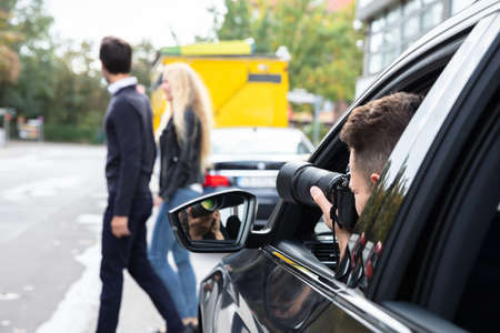 Private Detective Taking Photos Of Man And Woman On Street Stockfoto