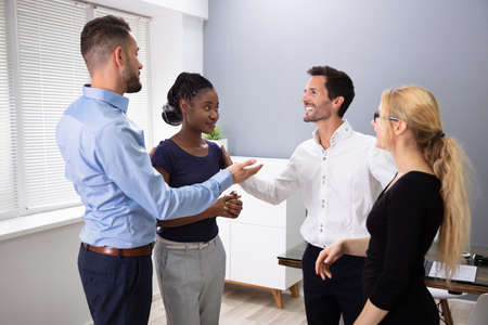Young Male Executive Introducing New Hire Employee To Corporate Team At Group Meeting Stock Photo