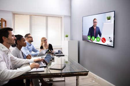 Los empresarios sentados en una sala de conferencias mirando la pantalla del ordenador Foto de archivo