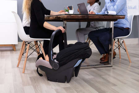 People Working Near Baby In Carrier On Hardwood Floor At Office