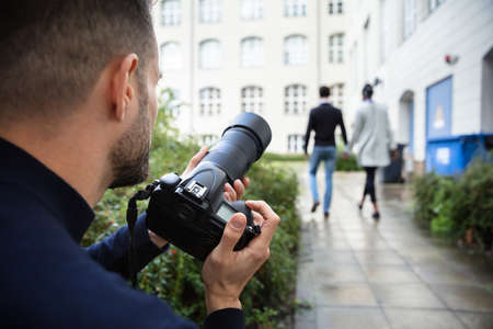 Joven fotógrafo paparazzi capturando una foto sospechosamente de una pareja caminando juntos usando una cámara