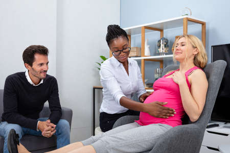 Peaceful Pregnant Woman Having A Relaxing Massage From African Female Therapist At Home
