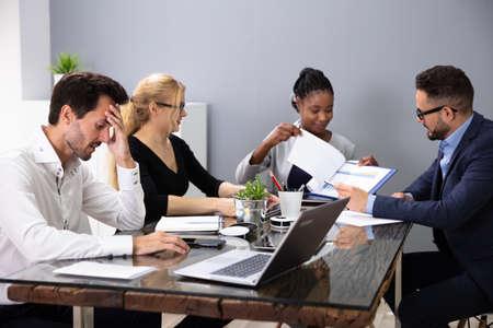 Pesebre macho aburrido sentado con sus colegas dando presentación en reunión en la oficina