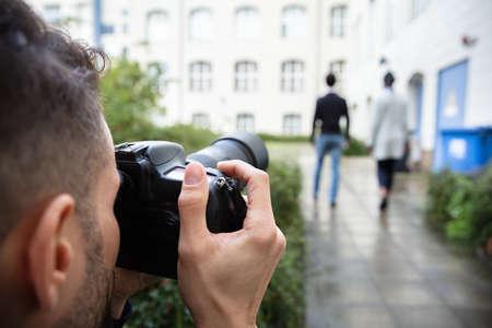 Jonge man Paparazzi-fotograaf die een verdachte foto vastlegt van een stel dat samen wandelt met behulp van een camera Stockfoto