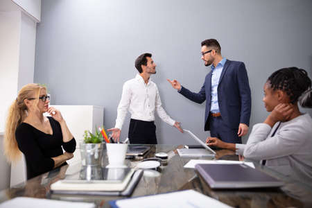 Dissatisfied CEO Shouting At His Young Male Worker For Bad Performance In Front Of Coworkers