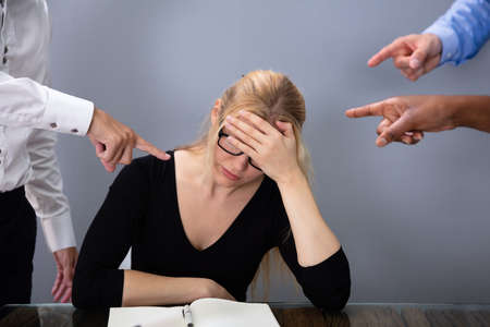 Business People's Hands Pointing At Stressed Businesswoman Leaning On Office Desk Archivio Fotografico