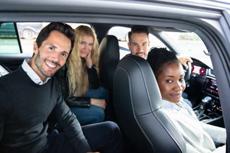 Happy Portrait Of Smiling Multi Racial Friends Sitting Inside Car