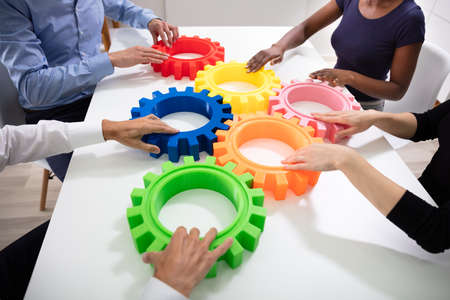 Group Of Businesspeople Arranging Colorful Cog Wheels Together Over White Table At Office