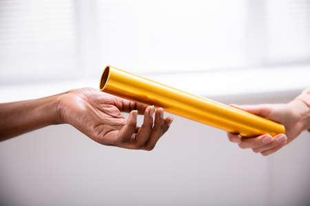 Nahaufnahme einer Hand, die goldenen Staffelstab an die Hand der afrikanischen Frau weitergibt