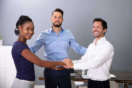Man Looking At Happy Business People Shaking Hands In Meeting Room