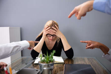 Business Peoples Hands Pointing At Stressed Businesswoman Leaning On Office Desk