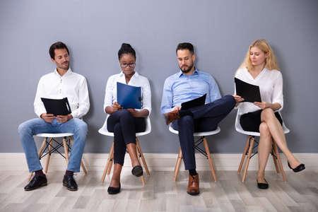 Empresarios multiétnicos sentados en sillas en fila esperando una entrevista de trabajo contra la pared gris