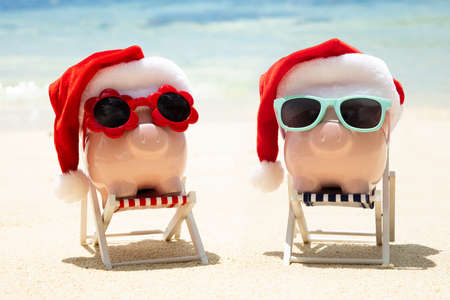 Close-up Of Two Pink Piggybank With Christmas Hats On Deck Chair At Beach