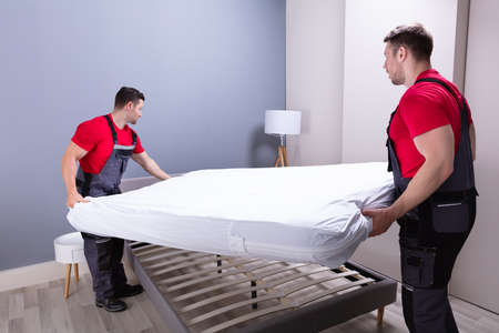 Two Male Professional Movers In Uniform Placing The Mattress Over The Bed In New House
