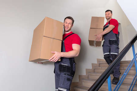 Portrait Of A Young Male Movers In Uniform Carrying Cardboard Boxes Walking Downward On Staircase