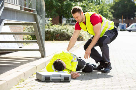 Worried Young Man Wearing Safety Jacket Looking At Person Falling On Street With Tool Box