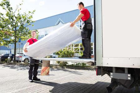 Jonge mannelijke verhuizers lossen de ingepakte matras uit de bewegende vrachtwagen