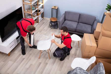 Deux jeunes hommes déménageurs emballant une chaise blanche avec une pellicule plastique dans le salon pendant le déménagement