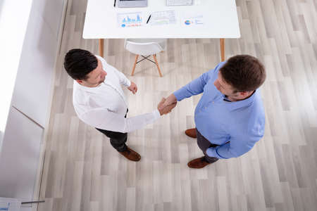 An Elevated View Of Two Businessmen Standing In The Office Shaking Hands Stock Photo