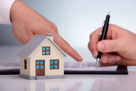 Miniature House In Front Of Buyer Signing A Home Purchase Agreement From A Broker Zdjęcie Seryjne