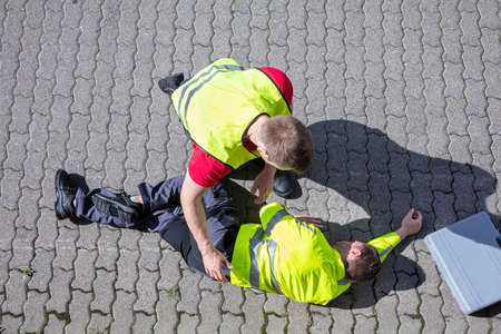 An Elevated View Of A Service Man Wearing Safety Jacket Looking At Unconscious Man