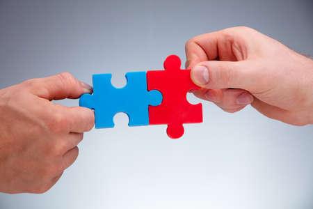 Nahaufnahme der Hand zweier Menschen, die weiße Puzzleteile auf grauem Hintergrund verbinden Standard-Bild