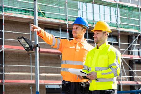 Męski nadzorca patrzący na architekta piszącego na schowku stojącego na placu budowy