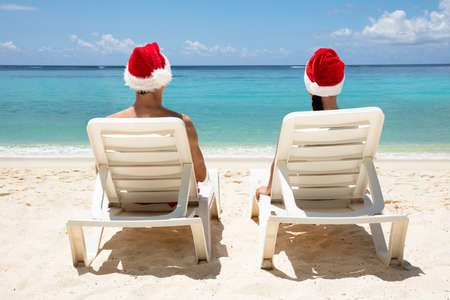 Rear View Of A Couple Wearing Santa Hats Relaxing On White Deck Chairs On Beach Stock Photo