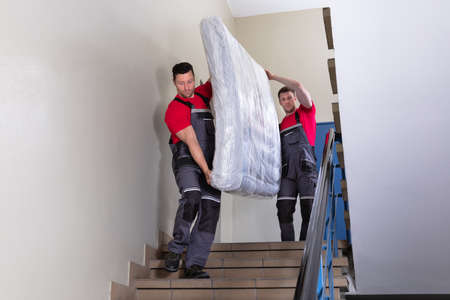 Two Young Male Movers In Uniform Carrying The Wrapped Mattress While Moving Downward The Staircase