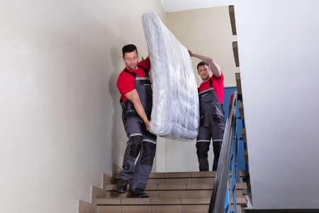 Zwei junge männliche Umzugshelfer in Uniform, die die eingewickelte Matratze tragen, während sie sich die Treppe nach unten bewegen