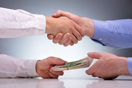 Close-up Of Businessmen Sealing The Deal With Handshake And Receiving A Bribe Money Stock Photo
