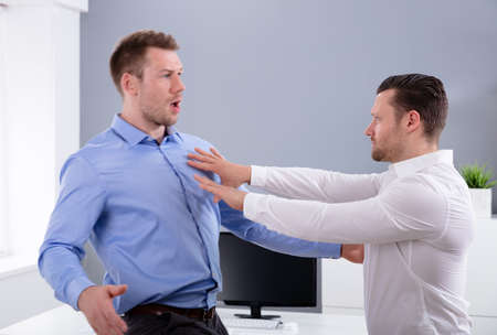 Two Angry Young Businessmen Quarreling With Each Other Fighting In The Office