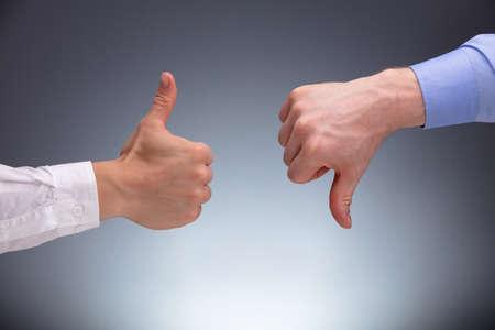 Close-up van twee zakenmanhanden die duimen omhoog en omlaag tonen tegen een grijze achtergrond