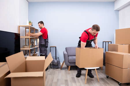 Two Young Movers In Uniform Picking And Putting Products In The Cardboard Boxes