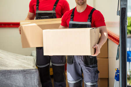 Happy Young Male Movers Holding Cardboard Boxes Standing In Moving Van Stock Photo