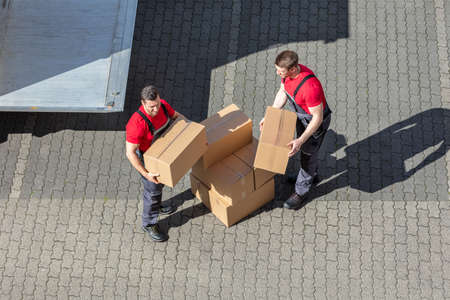 An Elevated View Of Two Young Male Movers Walking With Cardboard Boxes On Cobblestone Pavement Stockfoto