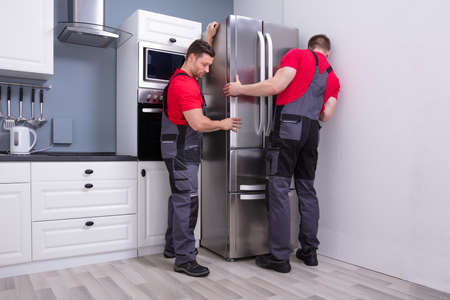 Two Young Male Movers In Uniform Placing Modern Steel Refrigerator In Kitchen Stockfoto
