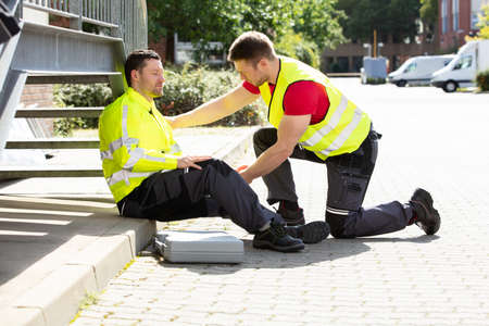 Young Man Wearing Safety Jacket Helping The Technician Feeling Dizziness On Street