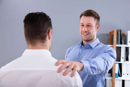 Portrait Of A Young Smiling Boss Congratulating Colleague For His Success