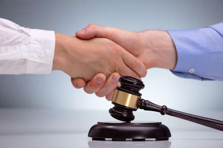 Mallet And Sound Block In Front Of Attorney Shaking Hand To Client After Meeting