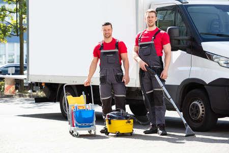 Zwei junge männliche Hausmeister mit Reinigungsgeräten stehen gegen LKW auf der Straße Standard-Bild