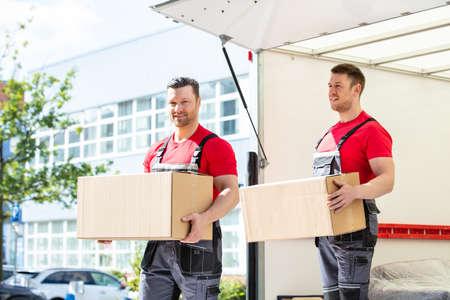 Heureux jeunes hommes déménageurs tenant des boîtes en carton debout dans un fourgon de déménagement Banque d'images