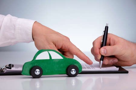 Close-up Of Mans Hand Signing Sales Contract For Car At Dealership Against Gray Background
