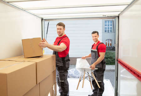 Portrait Of Smiling Young Male Movers Arranging The Products In Van