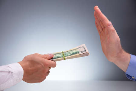 Close-up Of A Businessman's Hand Refusing Bribe Offered By His Partner Against Gray Background Stock Photo