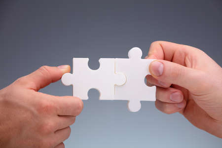 Close-up Of Two Peoples Hand Joining White The Jigsaw Puzzles Pieces On Gray Background